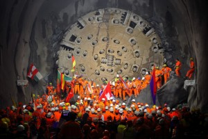 Miners hold national flags stand next to a giant drilling machine that completed the world