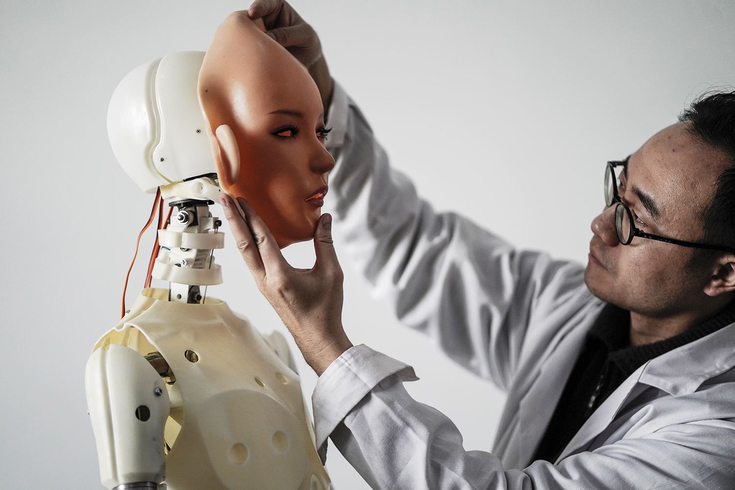 """This photo taken on February 1, 2018 shows an engineer holding a silicon face against the head of a robot at a lab of a doll factory of EXDOLL, a firm based in the northeastern Chinese port city of Dalian. With China facing a massive gender gap and a greying population, a company wants to hook up lonely men and retirees with a new kind of companion: """"Smart"""" sex dolls that can talk, play music and turn on dishwashers. / AFP PHOTO / FRED DUFOUR / TO GO WITH China-sex-lifestyle, FOCUS by Joanna CHIU"""
