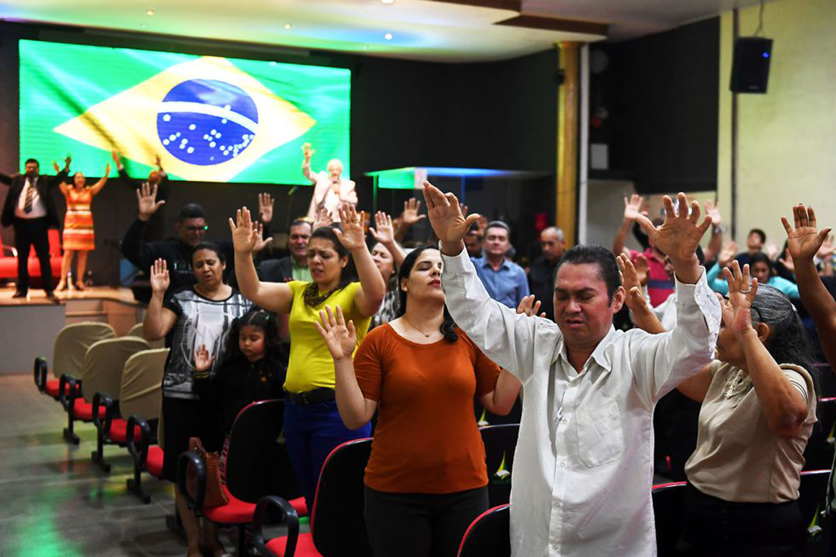 Factor religión - Feligreses de una iglesia evangélica en Brasilia orando para la recuperación del entonces candidato presidencial Jair Bolsonaro tras haber sido apuñalado en un evento público, en el 2018. (AFP)